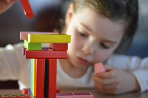 Girl building with blocks to illustrate how easy it is to build a website with WordPress